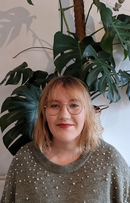 headshot of Roxane who is wearing a turquoise jumper with white pearls and gold rounded glasses. Roxane is white and has shoulder-length hair with a strawberry blond balayage. There is a big tropical plant and a white wall in the background.